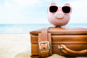 Pink piggy savings bank on a suitcase on the beach.