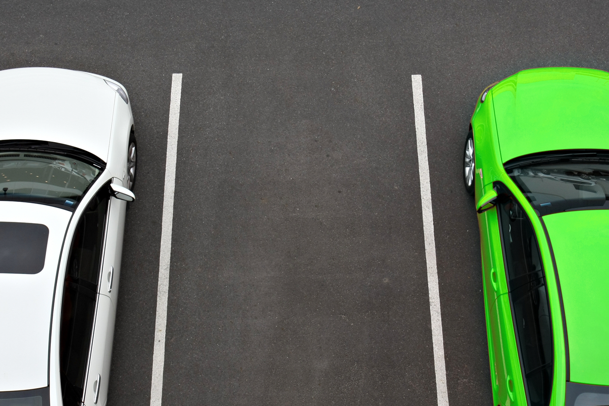 A white car and a green car parked at offsite airport parking facility.