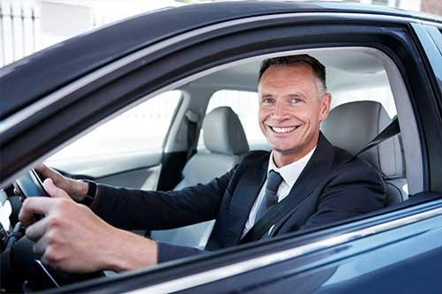 Business man driving a nice car.