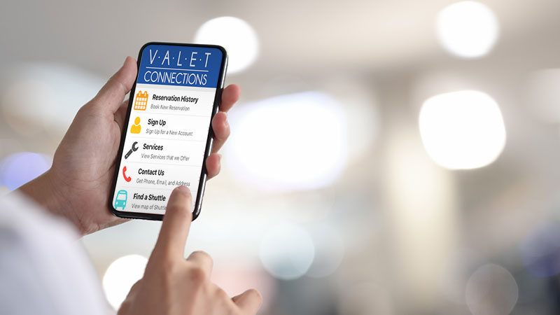 Hand holding phone with Valet Connections App on screen.