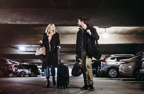 Couple walking in parking garage at DTW offsite parking.