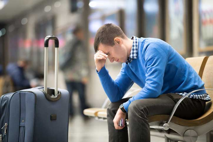 Man Sitting On Bench Lost At Airport